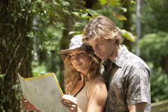 Couple with Map. Couple reading a map in a tropical forest royalty free stock photography