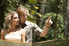 Couple with Map. Couple reading a map in a tropical forest stock photo