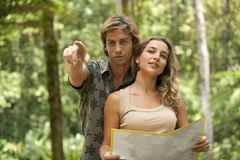 Couple with Map. Couple reading a map in a tropical forest stock photography