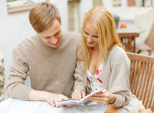 Couple with map, camera and city guide in cafe Stock Photography