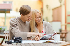 Couple with map, camera, city guide and coffee Stock Photos