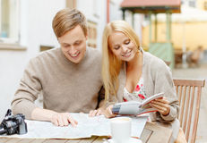 Couple with map, camera, city guide and coffee Royalty Free Stock Photo