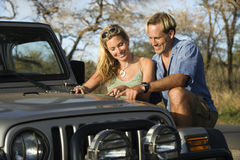 Couple With Map on Car Hood. A smiling man and woman look at a map spread out on the hood of a car. Horizontal format Stock Image