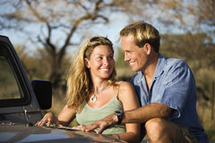 Couple With Map on Car Hood. A man and woman smile at each other as they share a map spread out on the hood of a car. Horizontal format Royalty Free Stock Photo