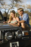 Couple With Map on Car Hood. A smiling man and woman look at a map spread out on the hood of a car. Vertical format Royalty Free Stock Photography