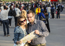 Couple with a Map in a Crowded City Royalty Free Stock Image