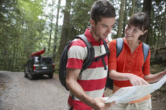 Couple With Map On Forest Road Stock Photo