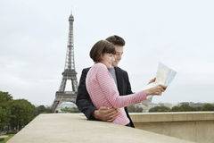 Couple With Map In Front Of Eiffel Tower. Side view of a young couple reading map on balcony in front of Eiffel Tower Royalty Free Stock Photo