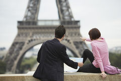 Couple With Map Looking At Eiffel Tower Royalty Free Stock Photography