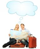 Couple with a map sitting on a suitcase Stock Photo