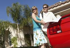 Couple With Map Standing By Car Stock Photography