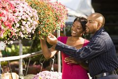 Couple at market. Happy smiling couple picking out flowers at outdoor plant market Royalty Free Stock Photo