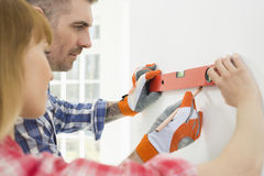 Couple marking on wall with level in new house royalty free stock image