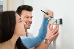 Couple marking on wall with level in new house Stock Photography