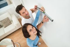 Couple marking on wall with level in new house Royalty Free Stock Photo