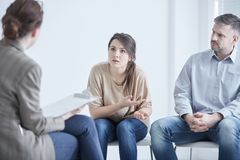 Couple on marriage therapy. Worried troubled couple on marriage therapy with psychologist Stock Photo