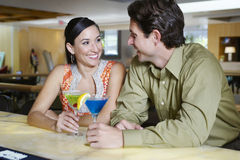 Couple With Martinis At Bar Counter Royalty Free Stock Photography