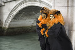 Couple of masks at bridge in Venice Royalty Free Stock Images