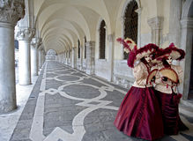Couple of masks under arcades in Venice Stock Photos