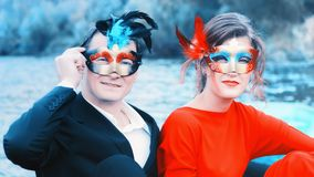 Couple In Masquerade Masks At A Lake. Colorful portrait of a young enamored couple in masquerade masks - men in a suit and women in red against a blue lake royalty free stock photography