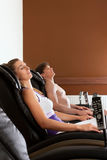 Couple on massage chair in gym Stock Photography