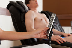 Couple on massage chair in gym Stock Image