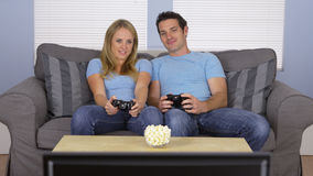 Couple in matching clothes playing video games Stock Images