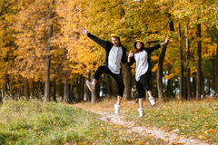 Couple in Matching Penguin Pajamas in autumn forest. Run and jump Stock Photography