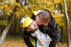 Couple in Matching Penguin Pajamas in autumn forest. Run and jump. the girl on the back men Royalty Free Stock Image