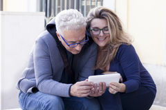 Couple of mature people consults the smartphone royalty free stock images