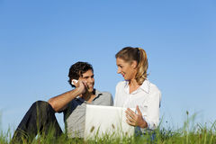 Couple on meadow with laptop and mobile phone stock image
