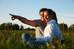 Couple on meadow in sunset royalty free stock photo