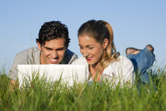 Couple on meadow using wi-fi for Internet stock image