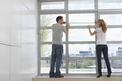 Couple Measuring Apartment Window Stock Photo