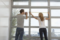 Couple Measuring Apartment Window Stock Image