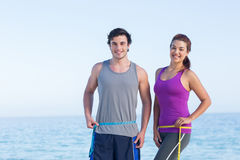 Couple measuring their waist Royalty Free Stock Images