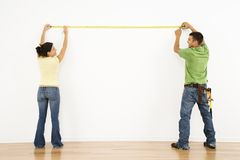 Couple Measuring Wall. Royalty Free Stock Photography