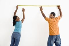 Couple measuring wall. Stock Photography