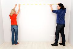Couple measuring wall Royalty Free Stock Image