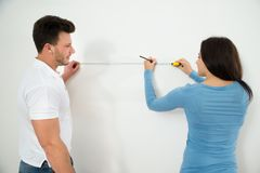 Couple measuring on wall with measuring tape Royalty Free Stock Photos