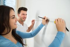 Couple measuring on wall with measuring tape Royalty Free Stock Images