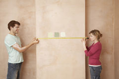 Couple Measuring Wall With Tape. Side view of couple measuring wall with tape Royalty Free Stock Photos