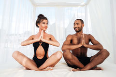 Couple mediating and sitting in lotus position on the beach Stock Photo