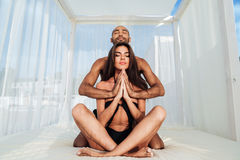 Couple mediating and sitting in lotus position on the beach Stock Images