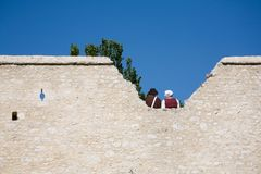 Couple in medieval costumes. Old fortress wall and couple in medieval costumes Royalty Free Stock Photography