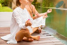 Couple meditate together. By the pool Royalty Free Stock Image
