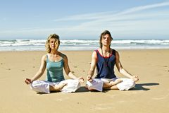 Couple meditating at the beach Stock Photos