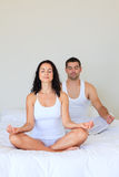 Couple meditating in bed Royalty Free Stock Images