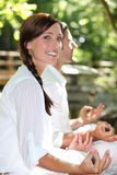 Couple meditating in garden Stock Images