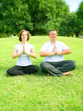 Couple Meditating In Park Stock Image